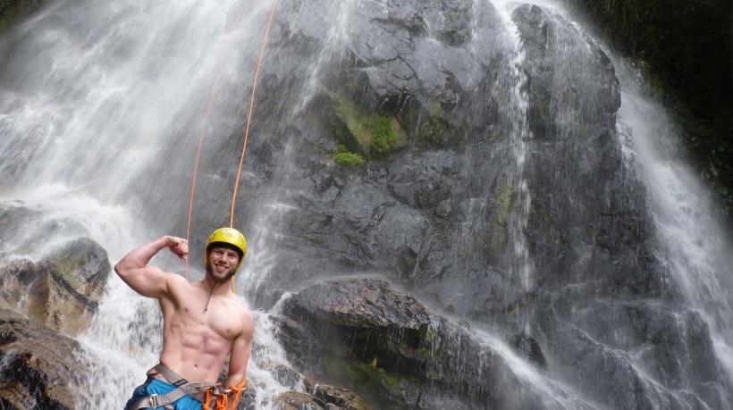 homem forte praticando rapel em cachoeira