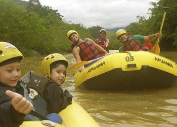 família em aventura com crianças fazendo rafting